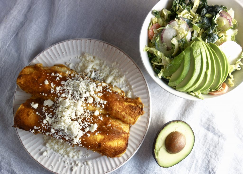 red sauce enchiladas with cheese on top on a white plate next to a salad with avocado