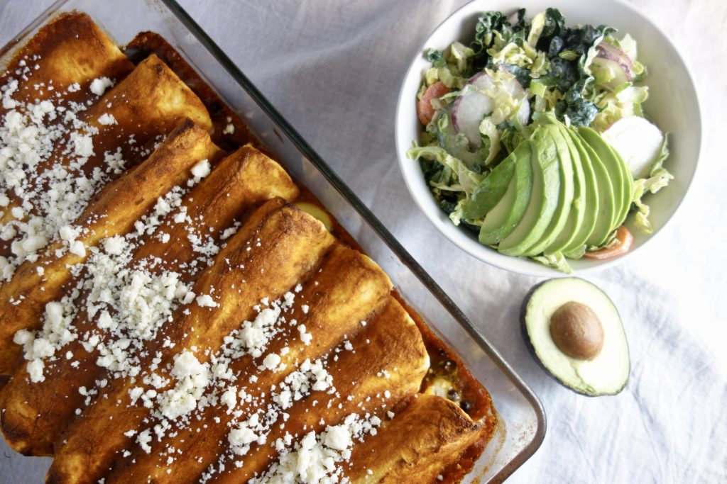 pan of red sauce enchiladas next to a salad with avocado on a white tablecloth