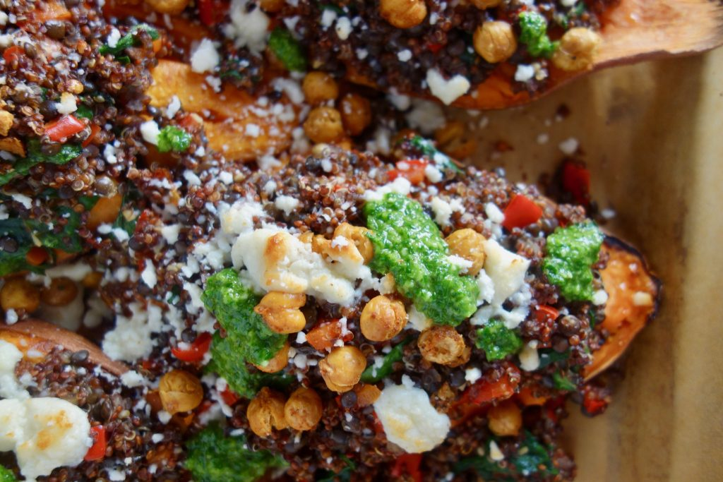 sweet potatoes on a pan with chickpeas, cheese and green sauce
