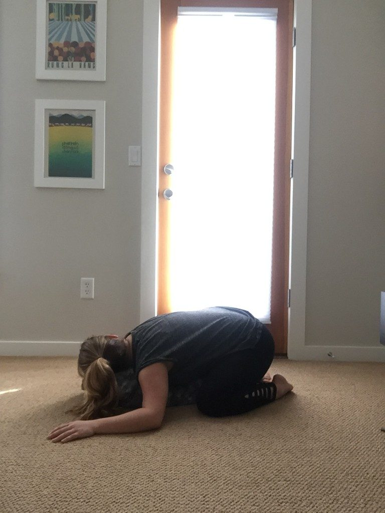 girl in a restorative yoga child's pose on the floor in front of a window
