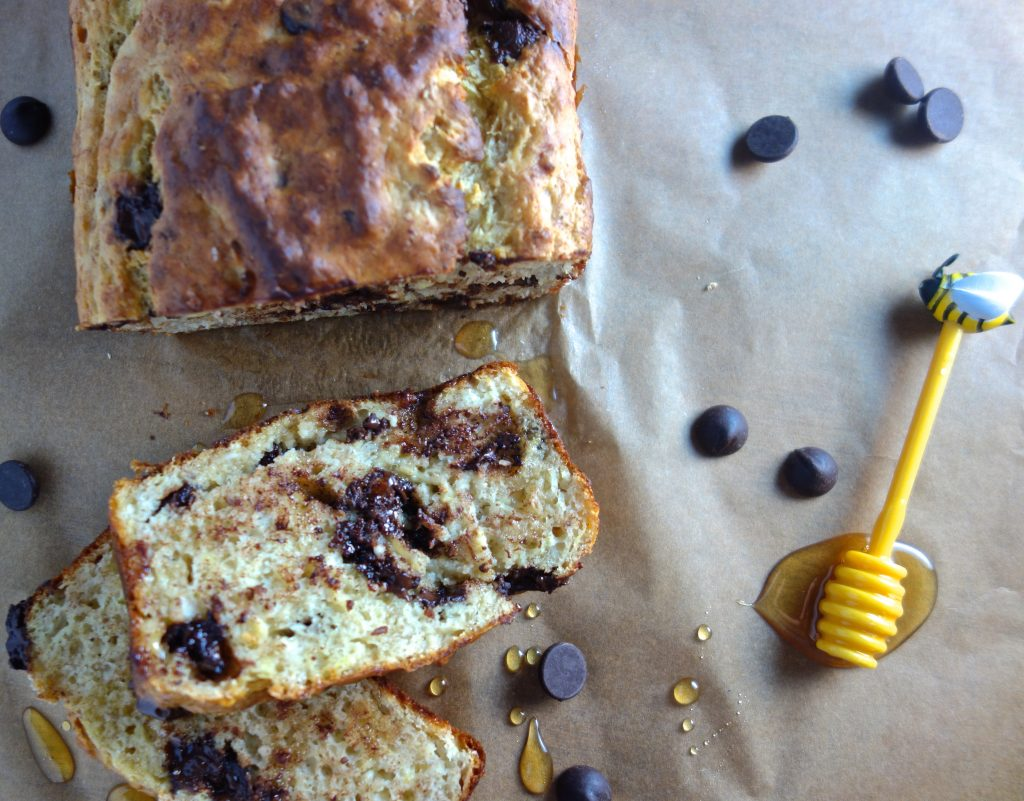 Warm banana bread made with honey and chocolate chips, sliced on parchment paper with a honey stick