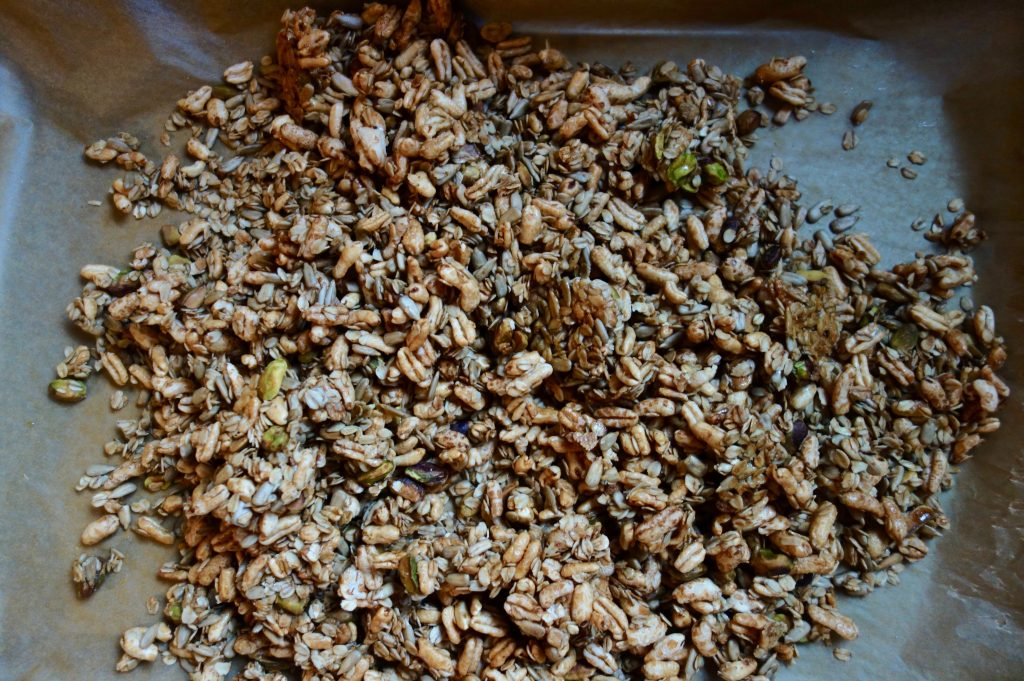 A top down view of crunchy and sweet granola with cashews, pistachios, sunflower seeds, maple syrup and kamut