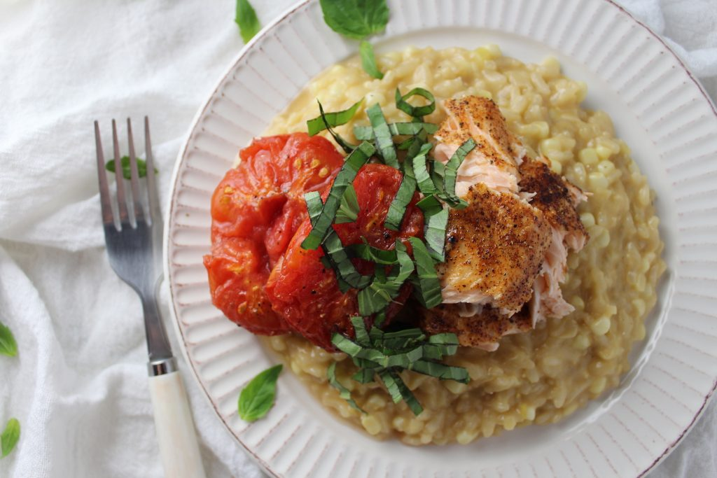 Corn Risotto with Roasted Salmon and Tomatoes on a white plate next to a fork