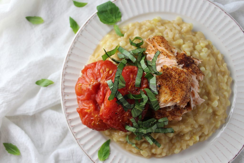 Corn Risotto with Roasted Salmon and Tomatoes on a white plate on a white table cloth