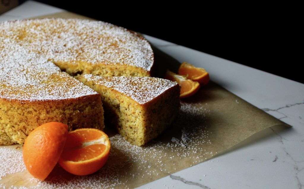 Clementine cake sitting on parchment paper on a counter next to sliced clementines
