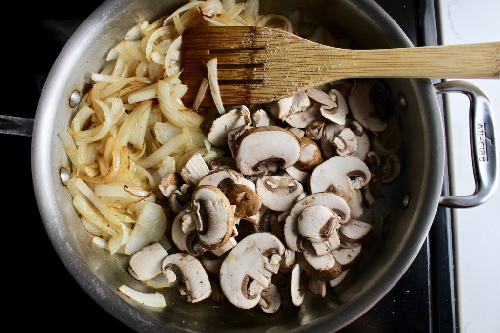 Onions and mushrooms cooking on a pan with a wooden spoon