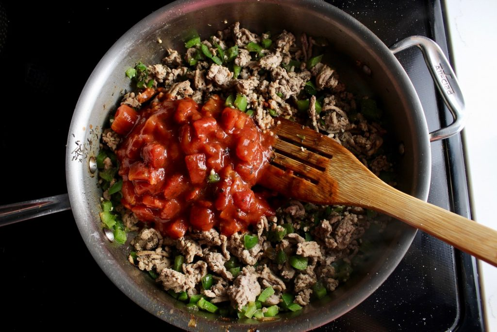 Turkey, peppers and tomato sauce cooking on a pan with a wooden spoon