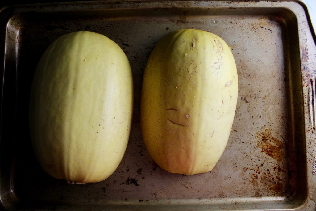 Two halves of spaghetti squash on a pan, face down