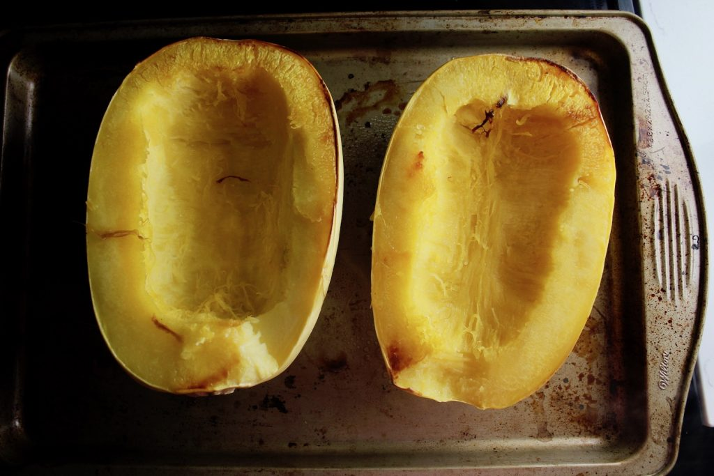 Two halves of spaghetti squash on a pan, face up