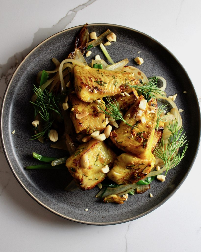 A top view of Vietnamese fish with turmeric and dill sitting on a dark plate