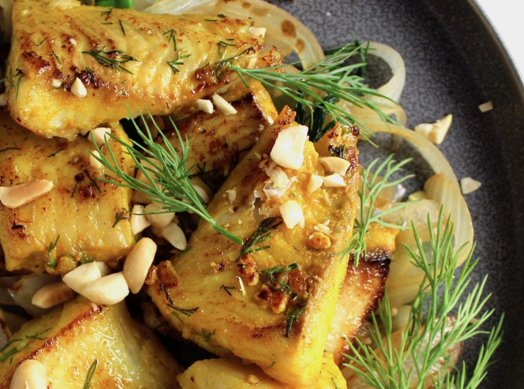 A close view of Vietnamese fish with turmeric and dill sitting on a dark plate