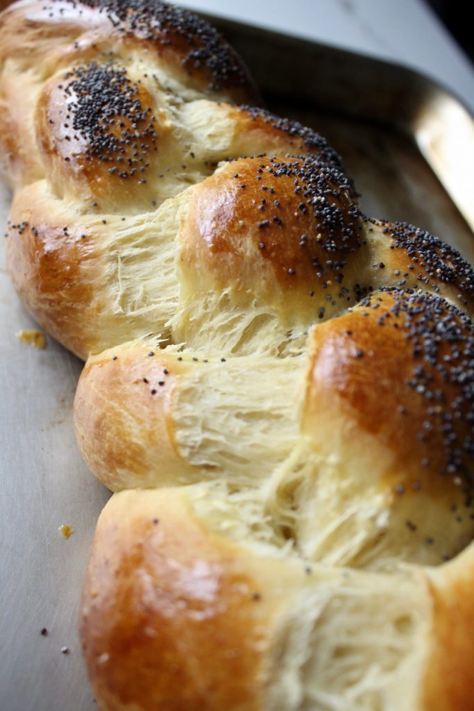 Basic Challah Bread on a sheet pan, braided and with a close up view