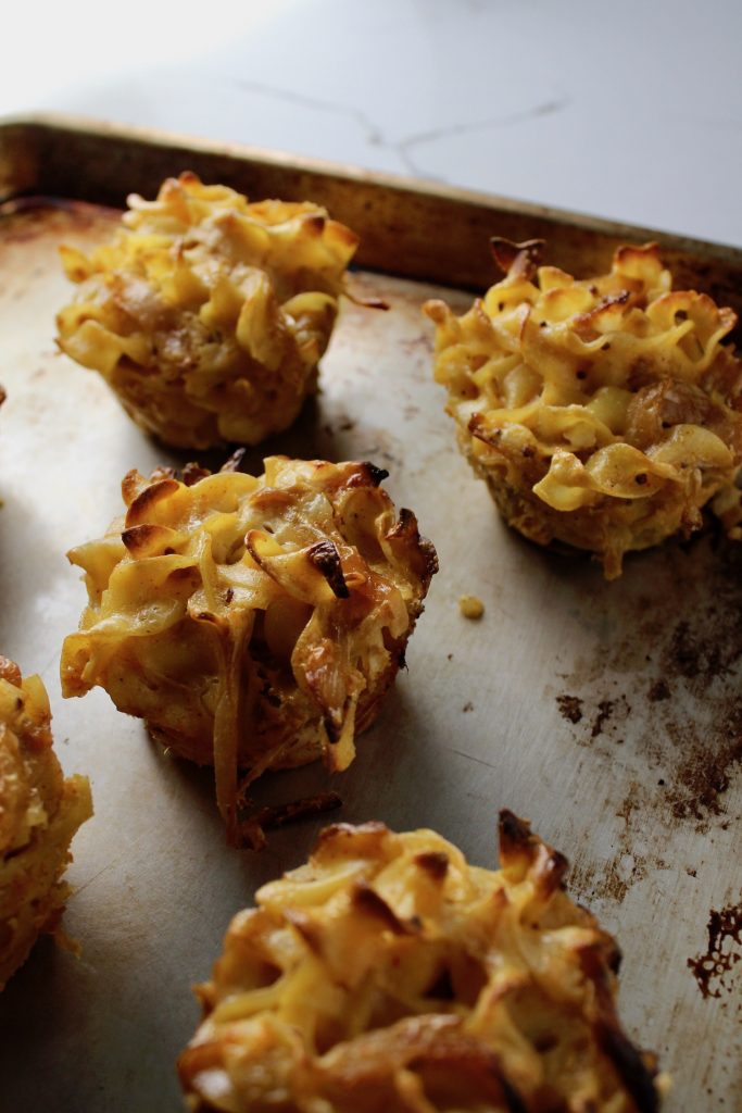 Savory Onion Crispy Kugel Cups sitting on a sheet pan on a counter top - side view