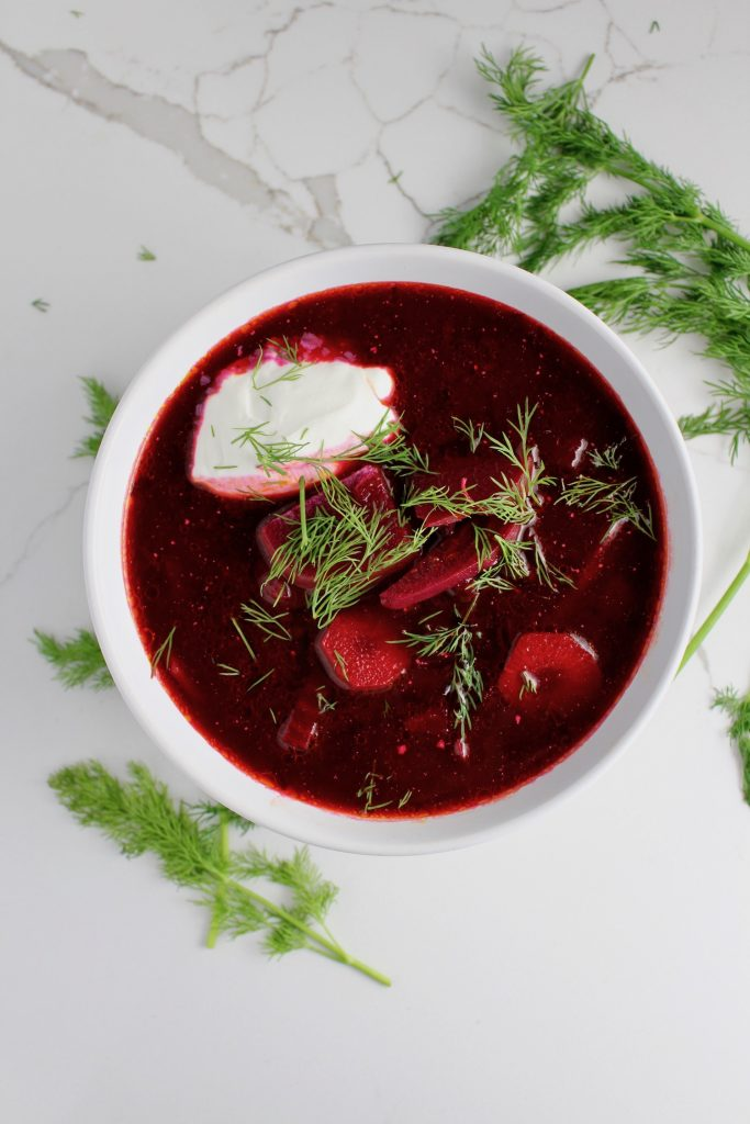 Top down picture of Classic Russian Borscht Soup on a white countertop with dill next to it