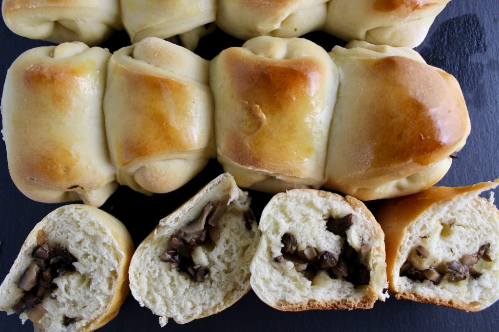 Top down view of baked mushroom piroshkis that have been sliced in half on a black slate board
