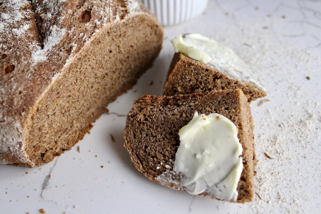 Russian Black Bread, sliced into chunks on a white countertop with a small bowl with butter