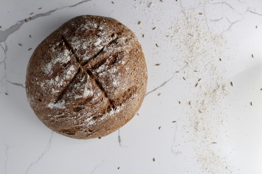 Russian black bread loaf on a countertop with flour and seeds