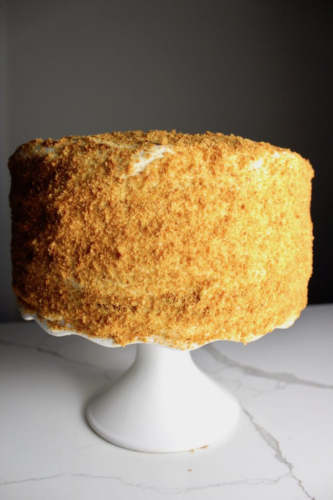 Russian honey cake sitting on a white cake stand, on a white countertop