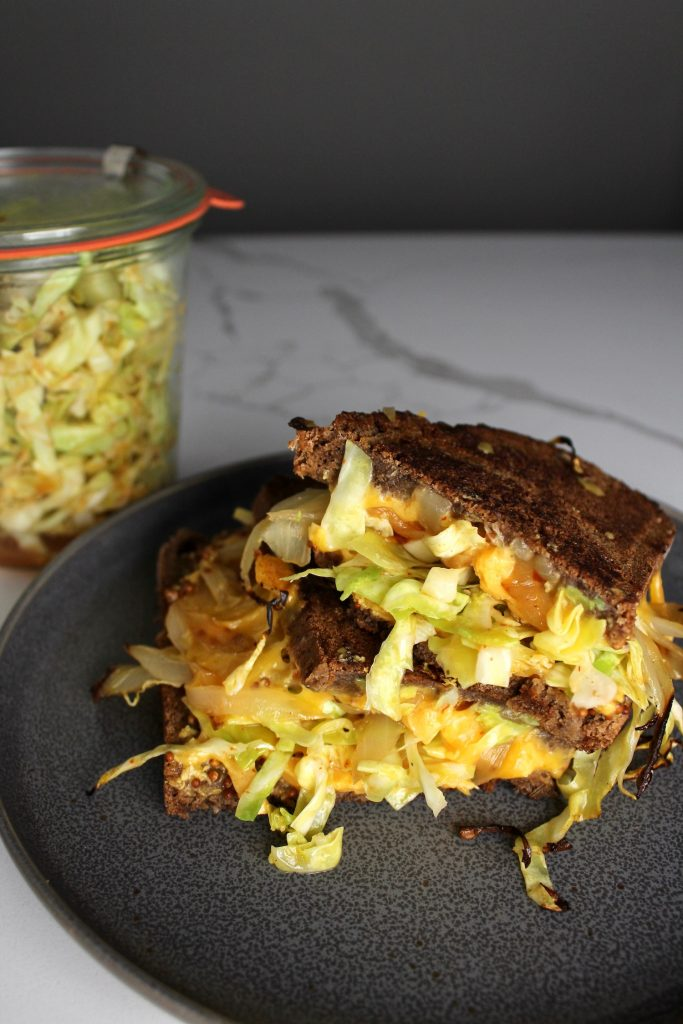 World's best sandwich on a dark plate, with spicy cabbage, onions, cheddar cheese, next to a jar of spicy cabbage