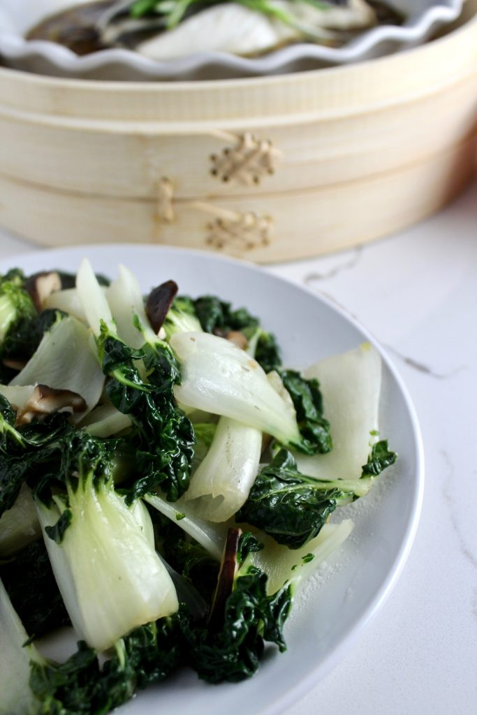 Bok Choy and Shiitake Mushrooms on a white plate on a white counter top next to a bamboo steamer basket