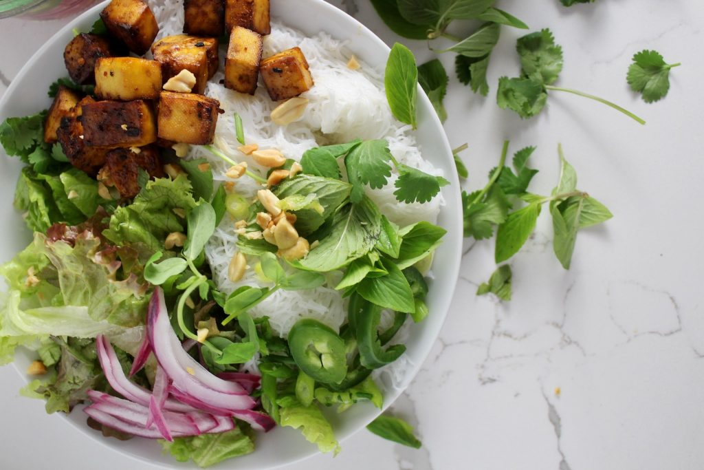 top down shot of a vietnamese bun bowl with greens and tofu on a white countertop