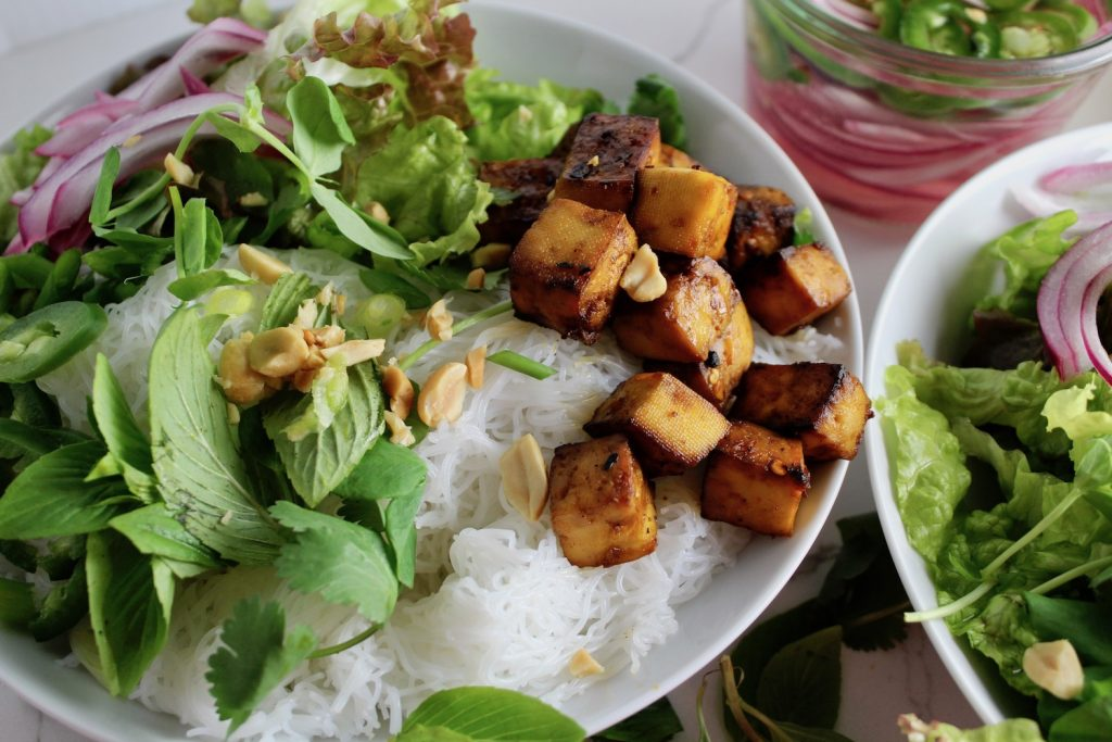 a side view of a vietnamese bun bowl with greens and tofu on a white countertop