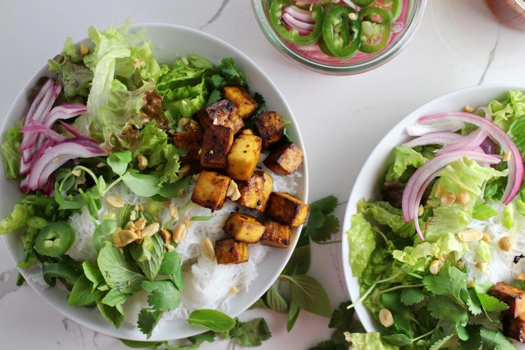 top down shot of two vietnamese bun bowls on a white countertop