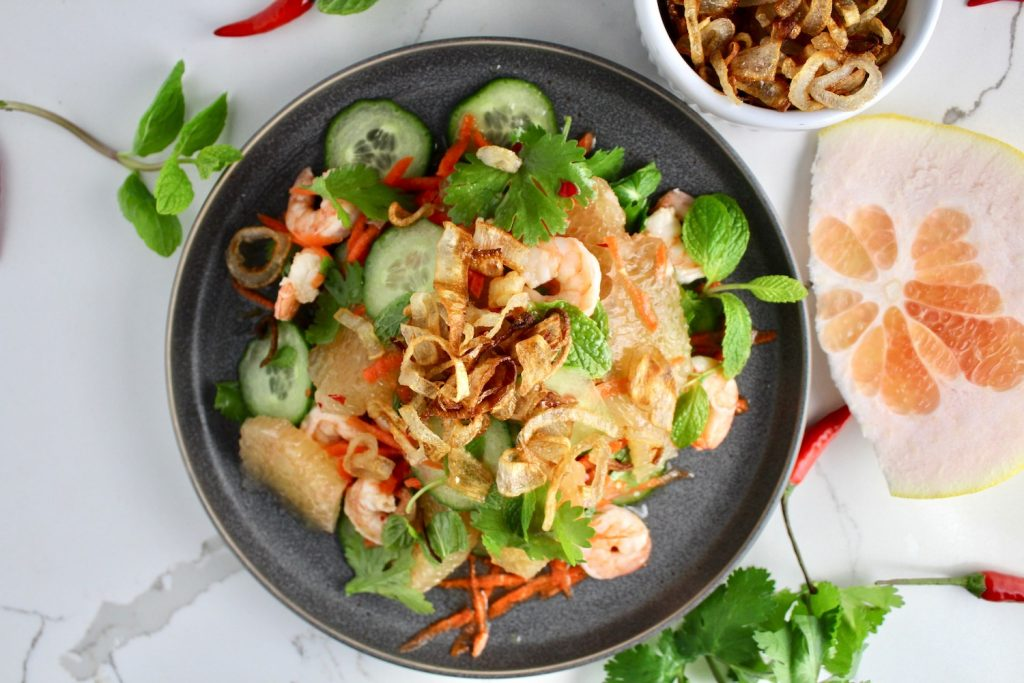 Vietnamese Pomelo Salad with fried shallots sitting on a white countertop next to a chili, pomelo and shallots