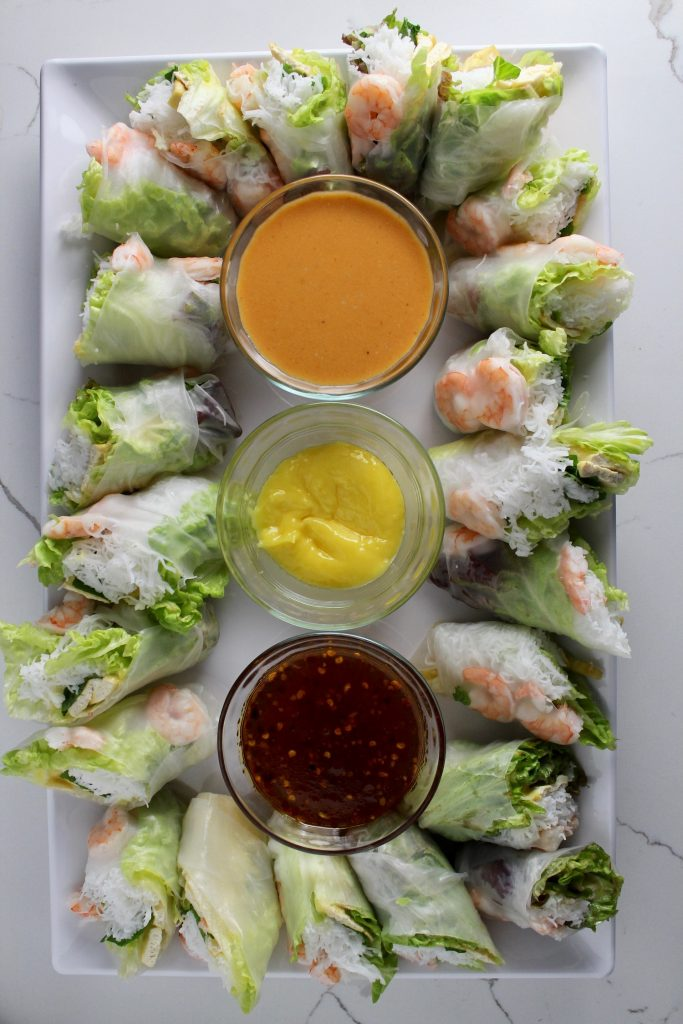 Spring Rolls and Peanut Sauce on a white platter sitting on a white countertop