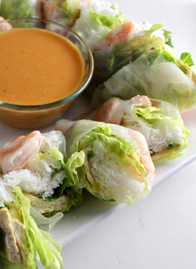 Spring rolls and peanut sauce on a white countertop