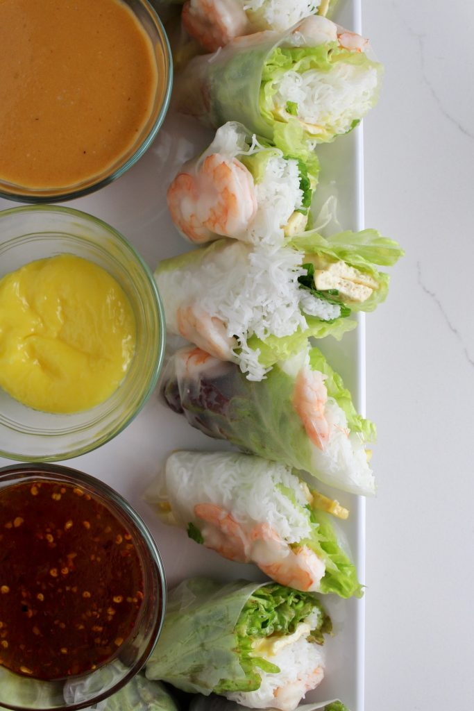 Spring rolls next to three sauces, sitting on a platter on a white countertop