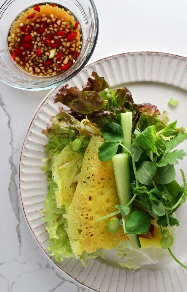 Wrapped Savory Vietnamese Crêpes sitting on a white plate next to greens and flavored fish sauce