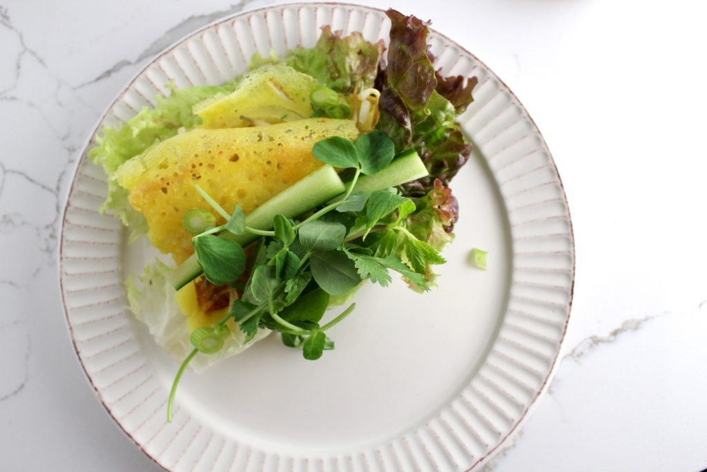 wrapped Savory Vietnamese Crêpes sitting on a white plate next to greens and flavored fish sauce on a white plate