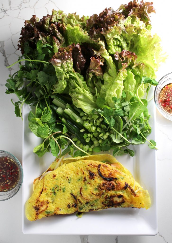 A spread of Savory Vietnamese Crêpes (Bánh Xèo) on a white plate with lettuce and herbs next to two bowls of flavored fish sauce