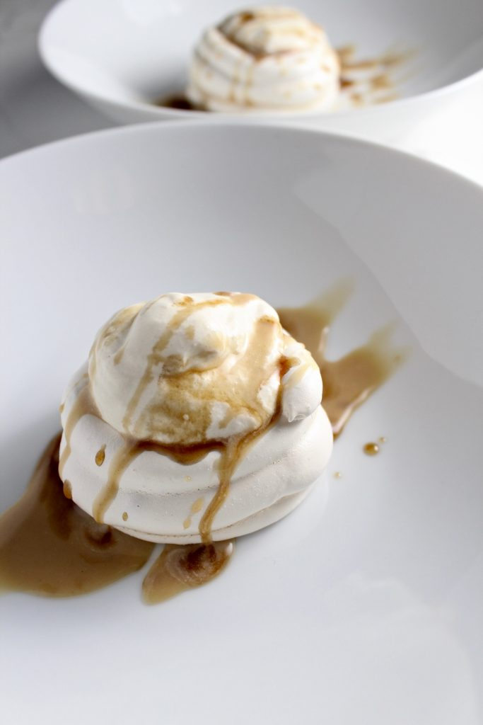 Mini Vietnamese Iced Coffee Pavlova sitting on a white plate on a white countertop