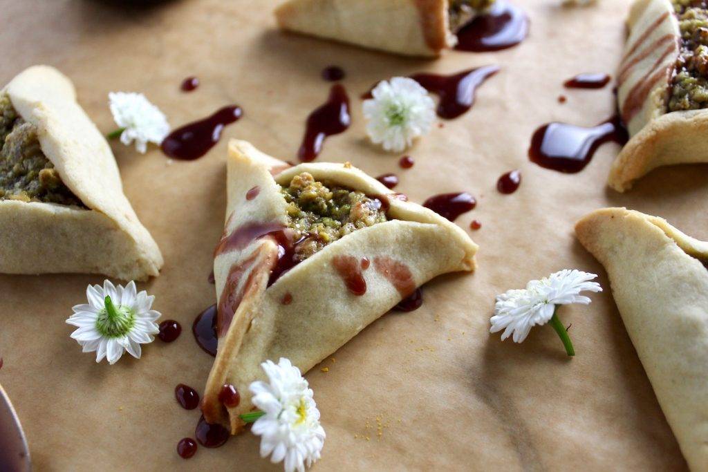 Pistachio Cardamom Rose Hamentaschen on parchment paper with Pomegranate Blood Orange Curd and white flowers next to