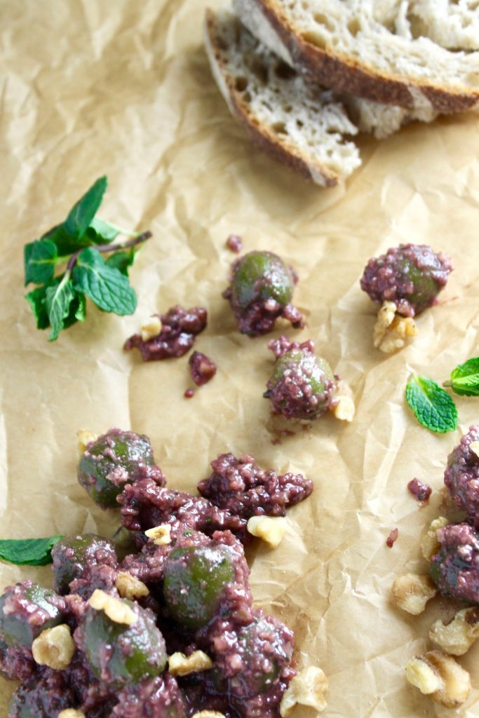 Zeytoon Parvardeh (Marinated Olives) on parchment paper with walnuts and mint