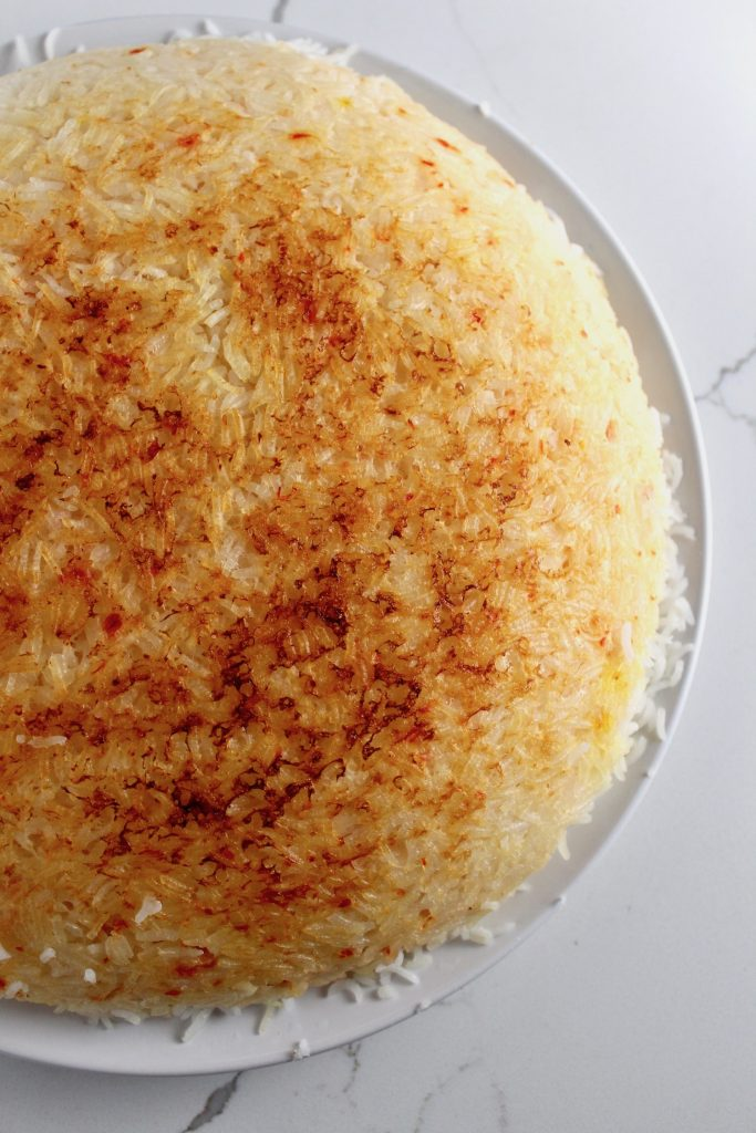 Tahdig (Persian Crispy Rice) is on a white plate on a white counter