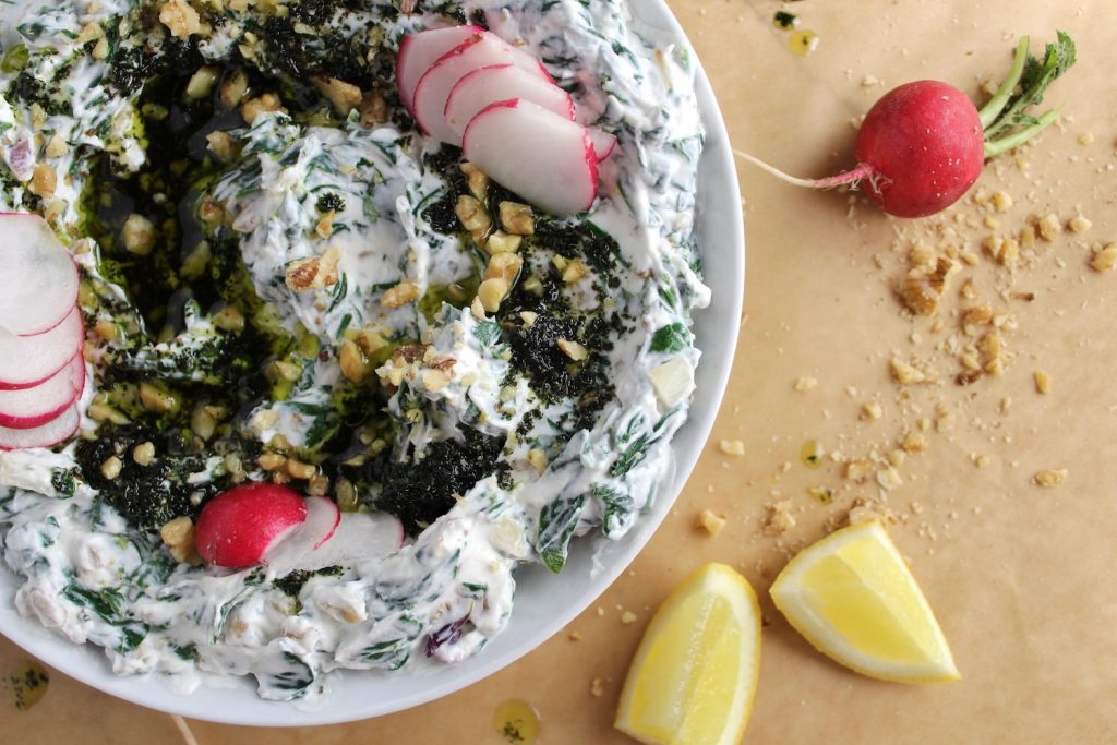 Borani Esfanaaj (spinach yogurt dip) in a white bowl with radishes on brown parchment paper next to lemons