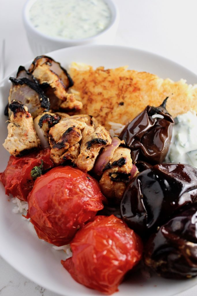 Tomatoes, Joojeh (chicken) kabobs, eggplant and mast-o-khiar over tahdig in a white bowl