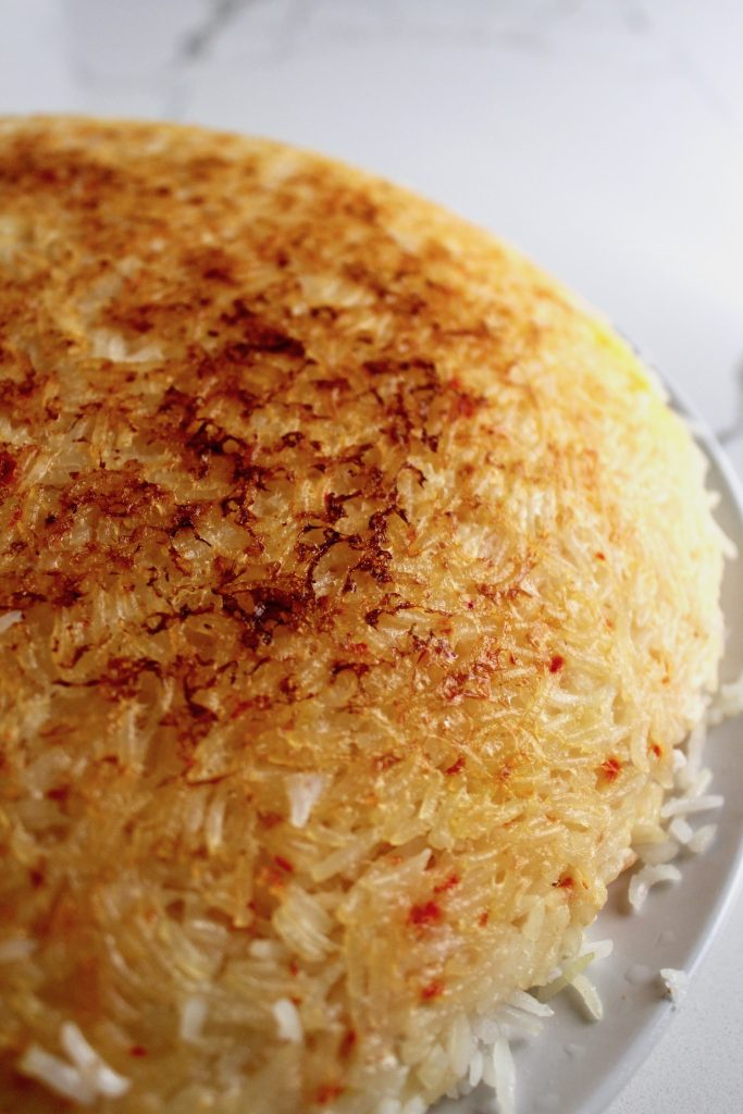 Tahdig (Persian Crispy Rice) is on a white plate on a white counter, side angle