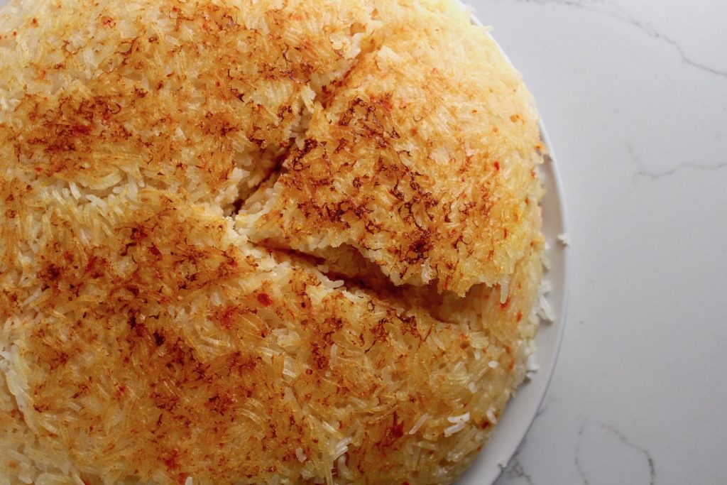Tahdig (Persian Crispy Rice) is on a white plate on a white counter, cut into a triangle