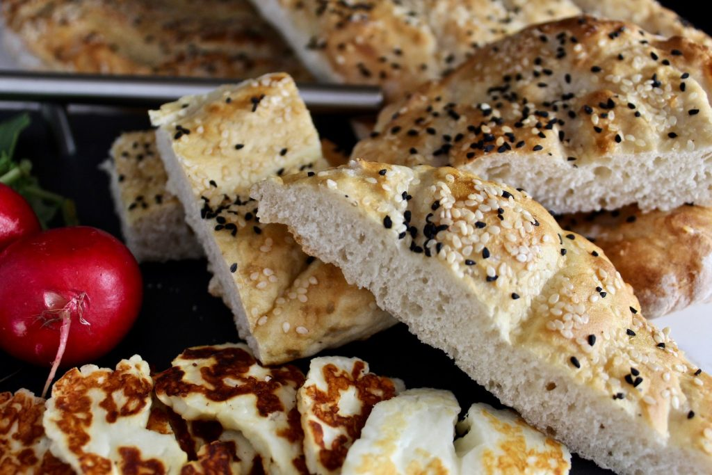Full loaves of persian barbari bread next to cut up pieces of bread