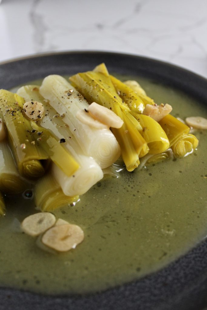 Slow cooked butter leeks on a grey plate with extra sauce and garlic
