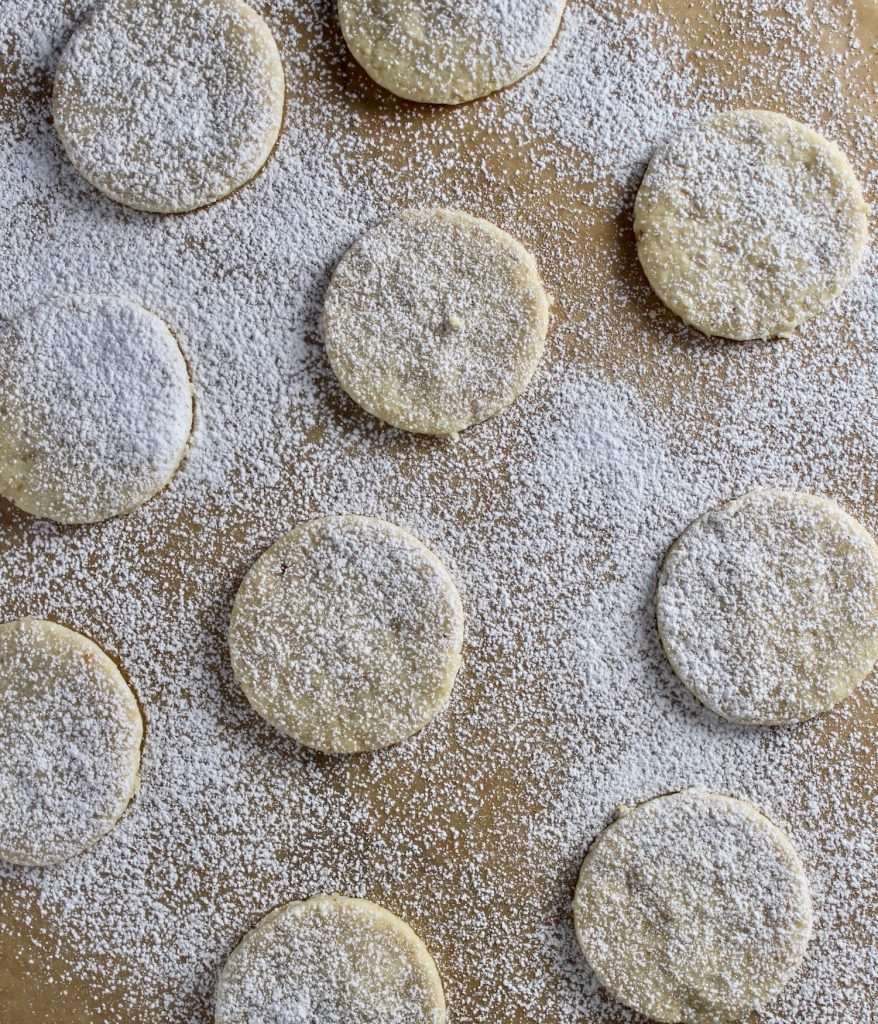 top down shot of many Hazelnut Shortbread Cookies on brown parchment with white powdered sugar dusted on top
