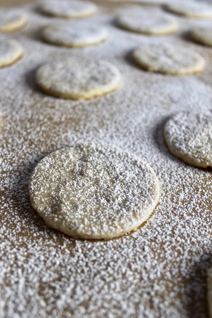 close up shot of one Hazelnut Shortbread Cookies on brown parchment with white powdered sugar dusted on top