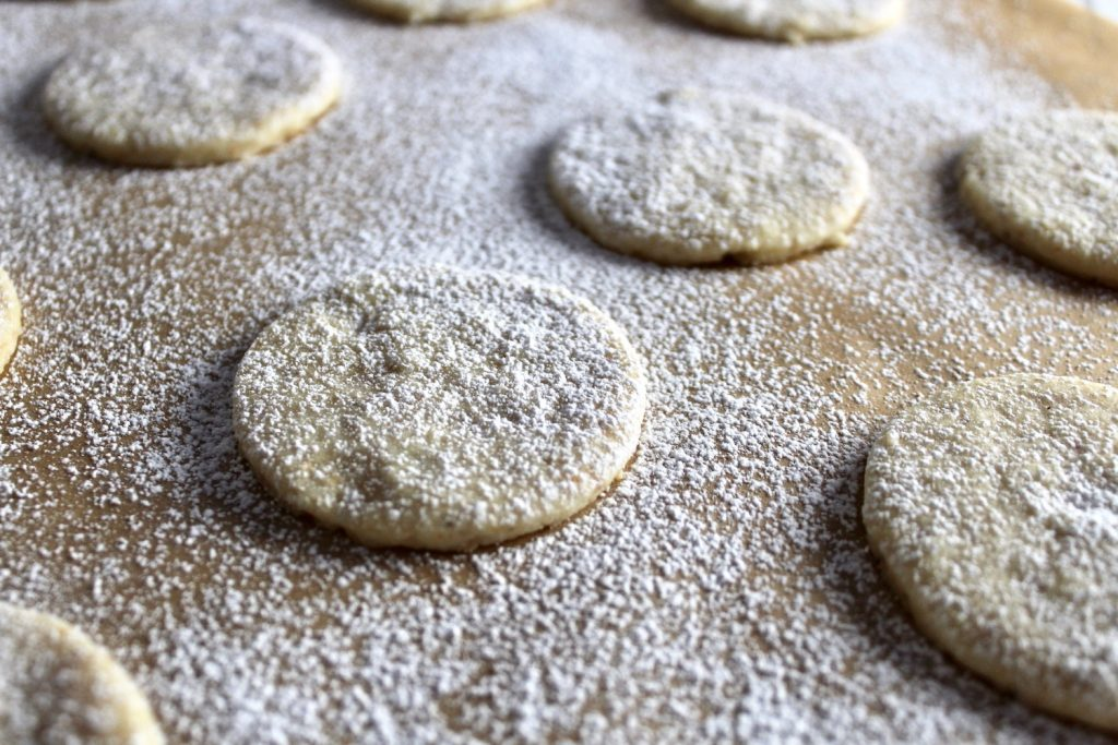 close up of a Hazelnut Shortbread Cookies on brown parchment with white powdered sugar dusted on top