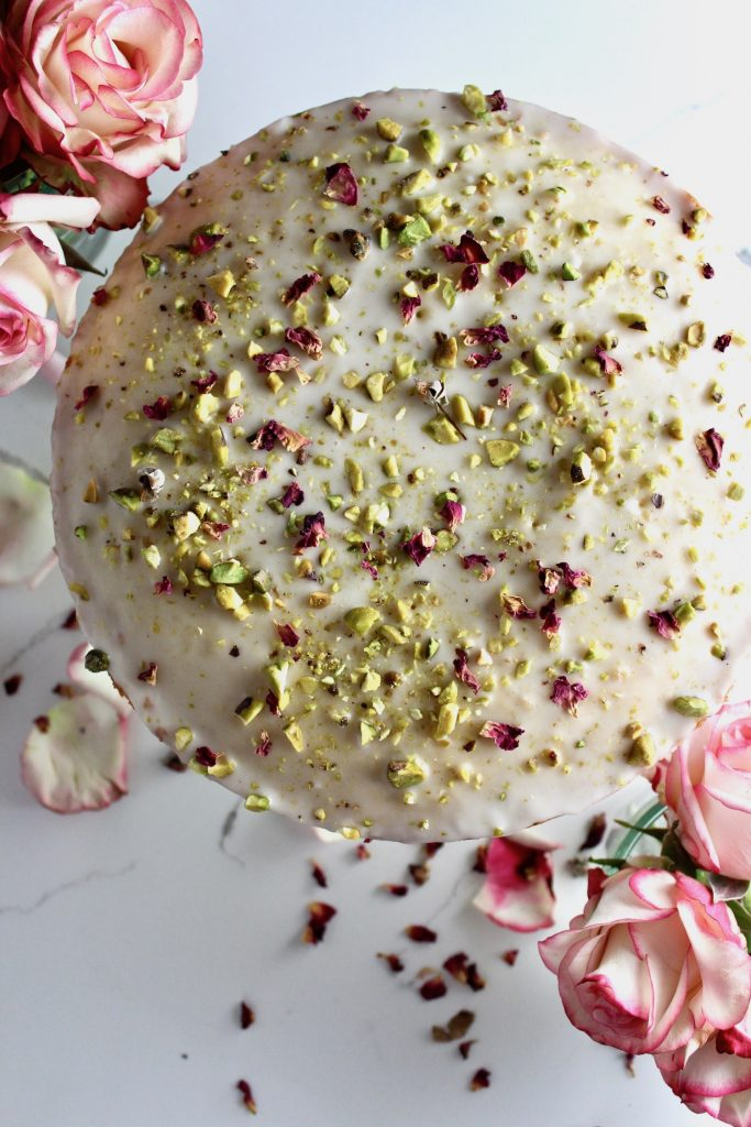 Top shot of persian love cake with roses and petals next to it