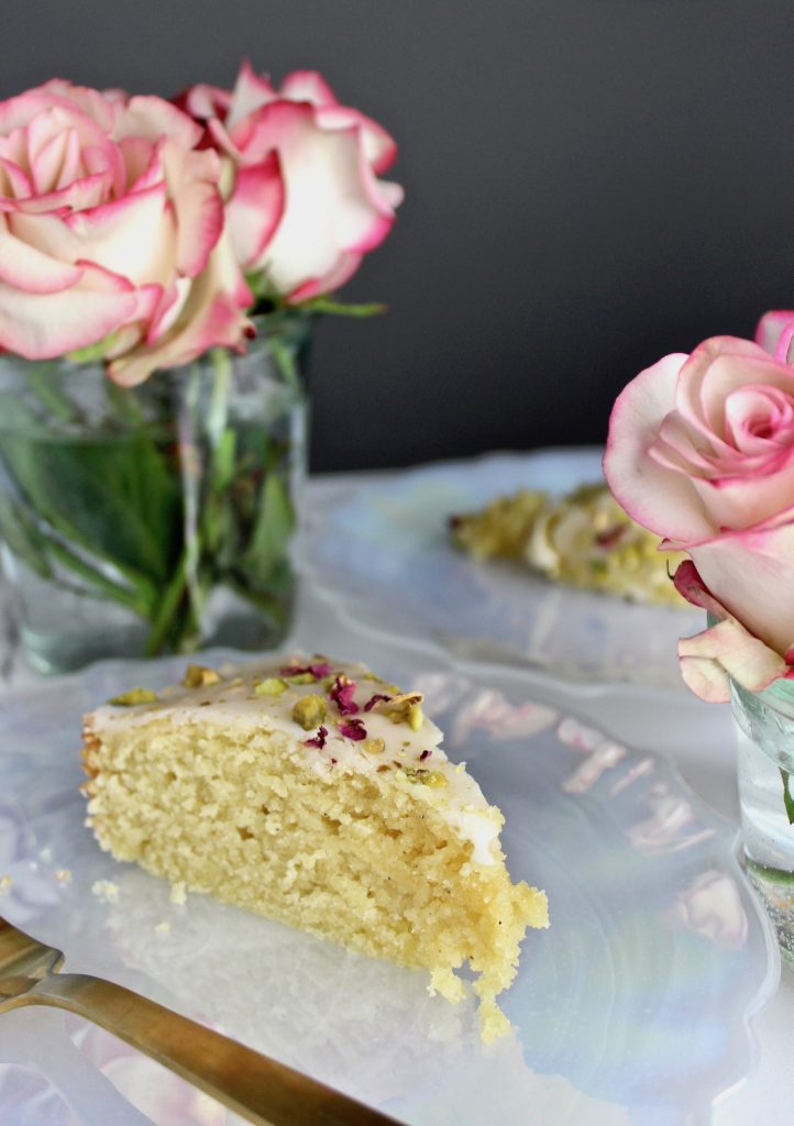 Slice of persian love cake on a white plate next to roses