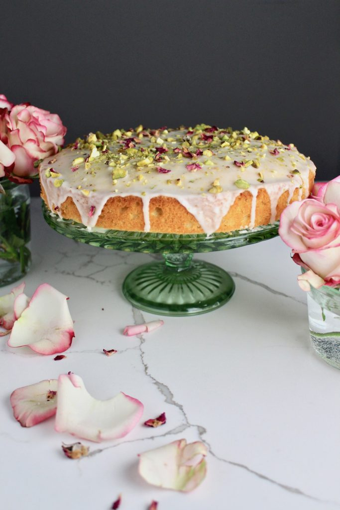 Side view of persian love cake with frosting dripping down, on a green cake stand next to roses on a white countertop